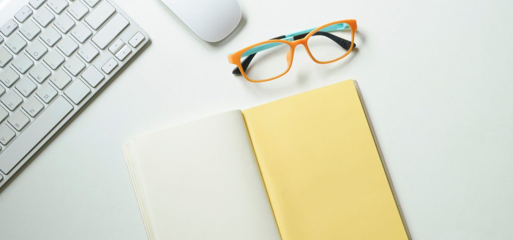 A photo of glasses on a desk with a keyboard and open notebook